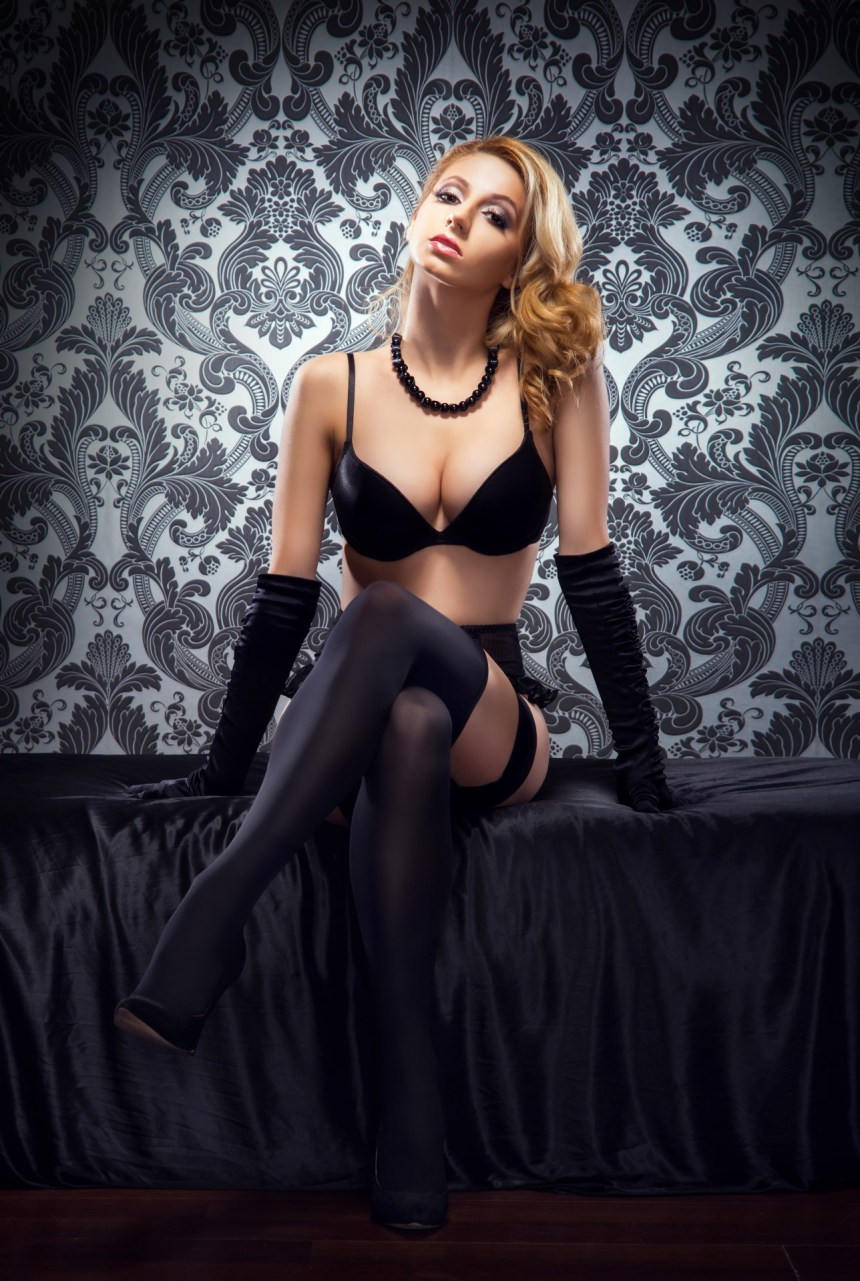 Young, sexy and beautiful woman in underwear in the bed over retro background.