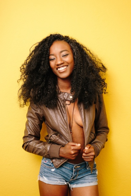 A beautiful young fit black woman with big natural curly hair wearing a brown leather jacket and blue short denim jean shorts isolated on yellow wall background