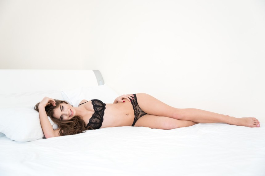 Happy cute woman in sexy lingerie lying on the bed and looking at camera