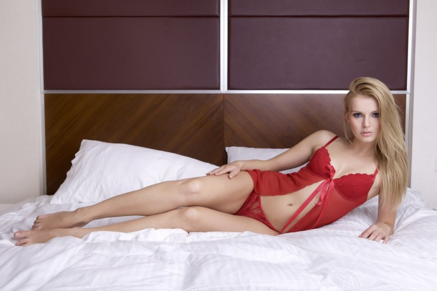 Young sexy blond woman in sexy red lingerie lying on the bed
